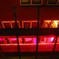 """A photo taken from a height looking down on the front of a building at night. There are red lights making a glow from the windows below, envoking the sense of a """"Red Light District""""."""