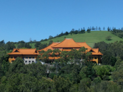 A landscape photo of the Nan Tien temple nestled amongst trees with a mountain in the background.