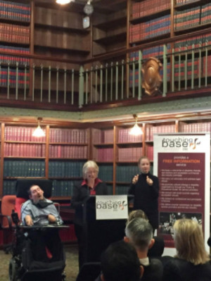 In a room with bookshelves from floor to ceiling – three people are facing an audience that you can only see the backs of the heads of. The people are Murray Louden sitting in a wheelchair, Iris Louden speaking at the rostrum and an Auslan interpreter, Jennifer MacLaughlan, to her left.