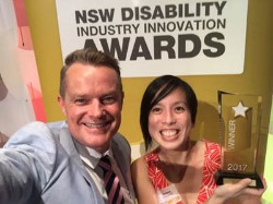 """Rob Hardy and Ee-Lin Chang holding a glass award under a sign saying """" NSW Disability Industry Innovation Awards"""""""