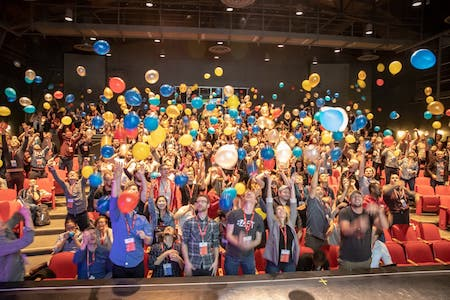 SmashingConf attendees playing with colored balloons at the opening ceremony