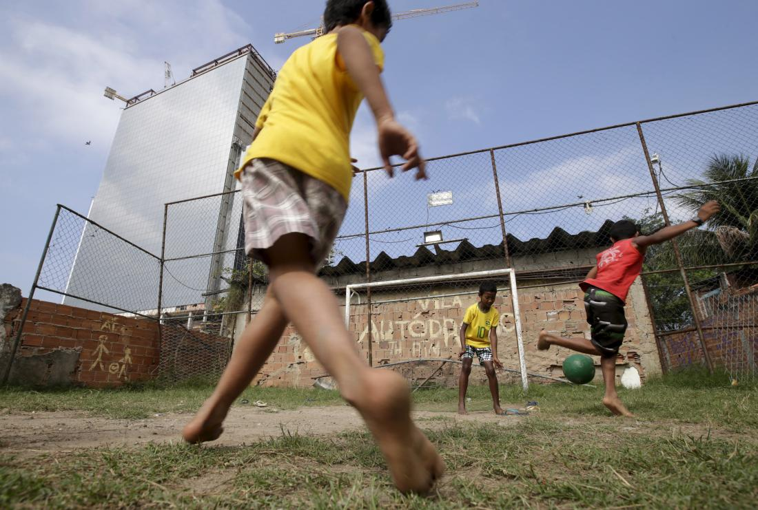 Ricardo Moraes—Reuters. Children play soccer in the Vila Autodromo slum in Rio de Janeiro on July 28, 2015.