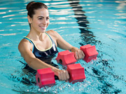 Woman in swimming pool holding water weights