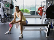 Woman sitting on weightlifting bench