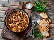 A hearty bowl of chili flanked by grilled bread
