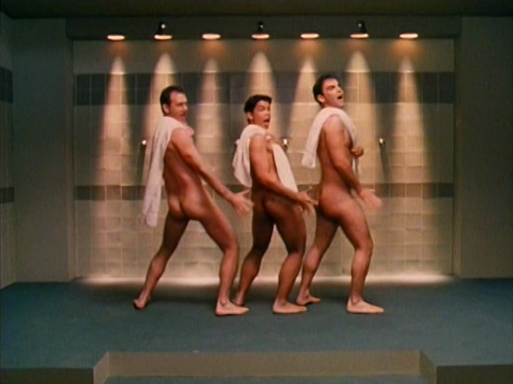 Three semi-nude men dancing and singing in a sauna