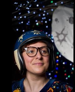 Image of a woman with glasses wearing a helmet, she is looking up at a homemade moon