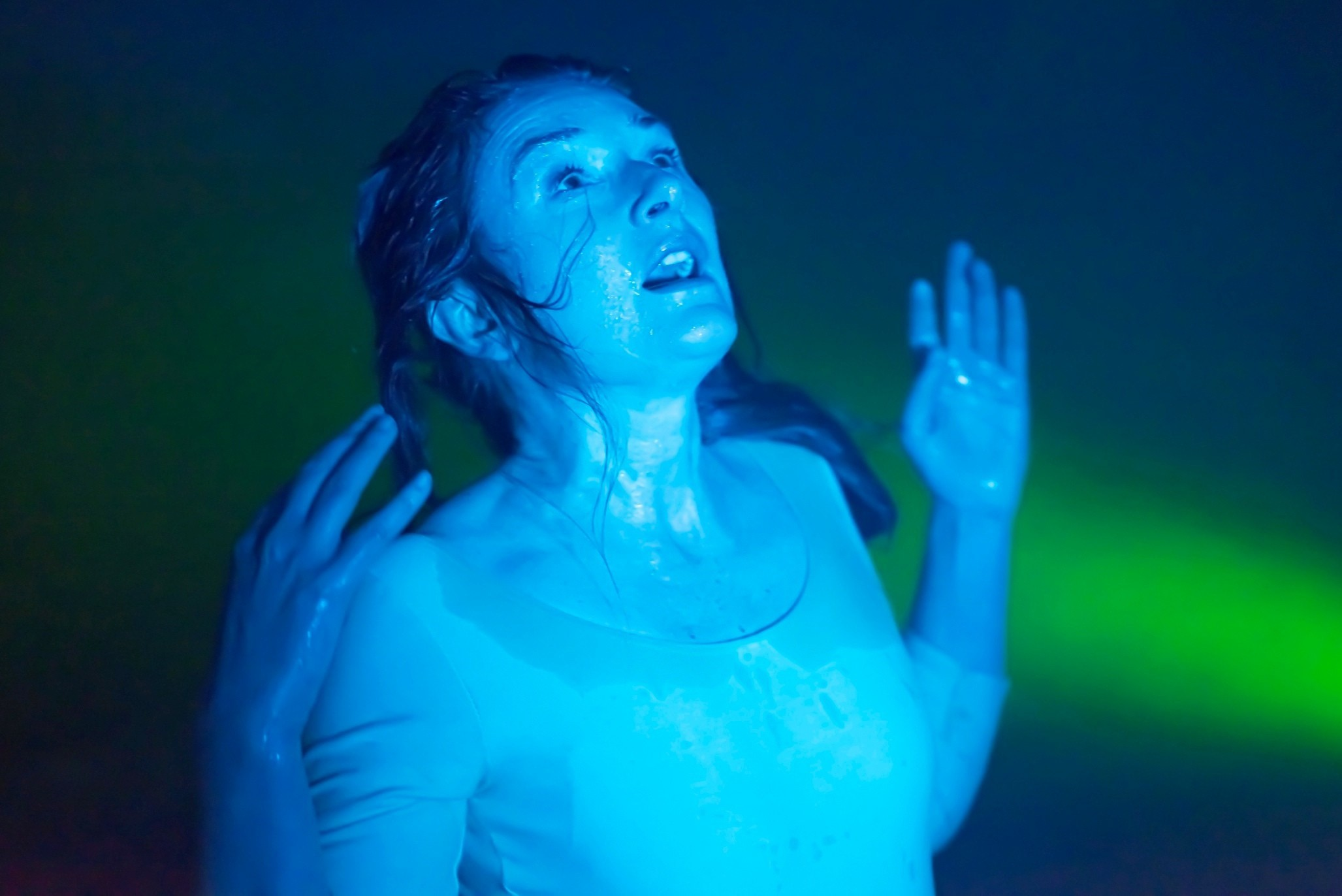 Image of a woman who appears sweaty of wet with her hand in the air, looking upwards, against a green and blue background