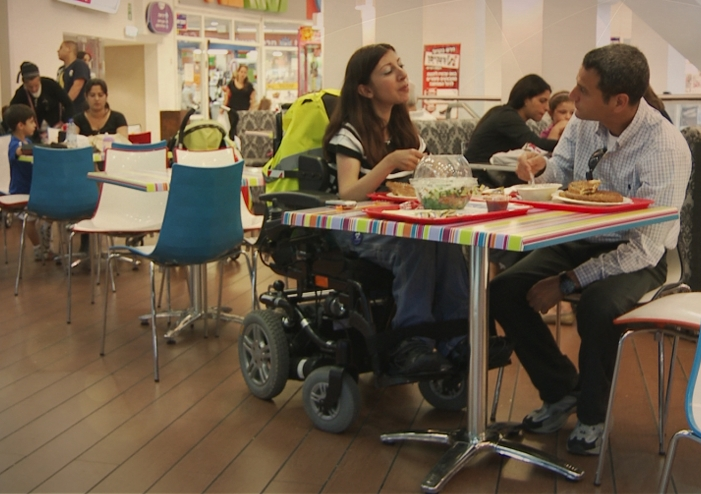 Image of a woman in an electric wheelchair and a man eating a meal together in a restaurant, it looks like they're on a date.