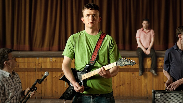 Still image from film Sons and Mothers, a man in a green t shirt holding an electric guitar