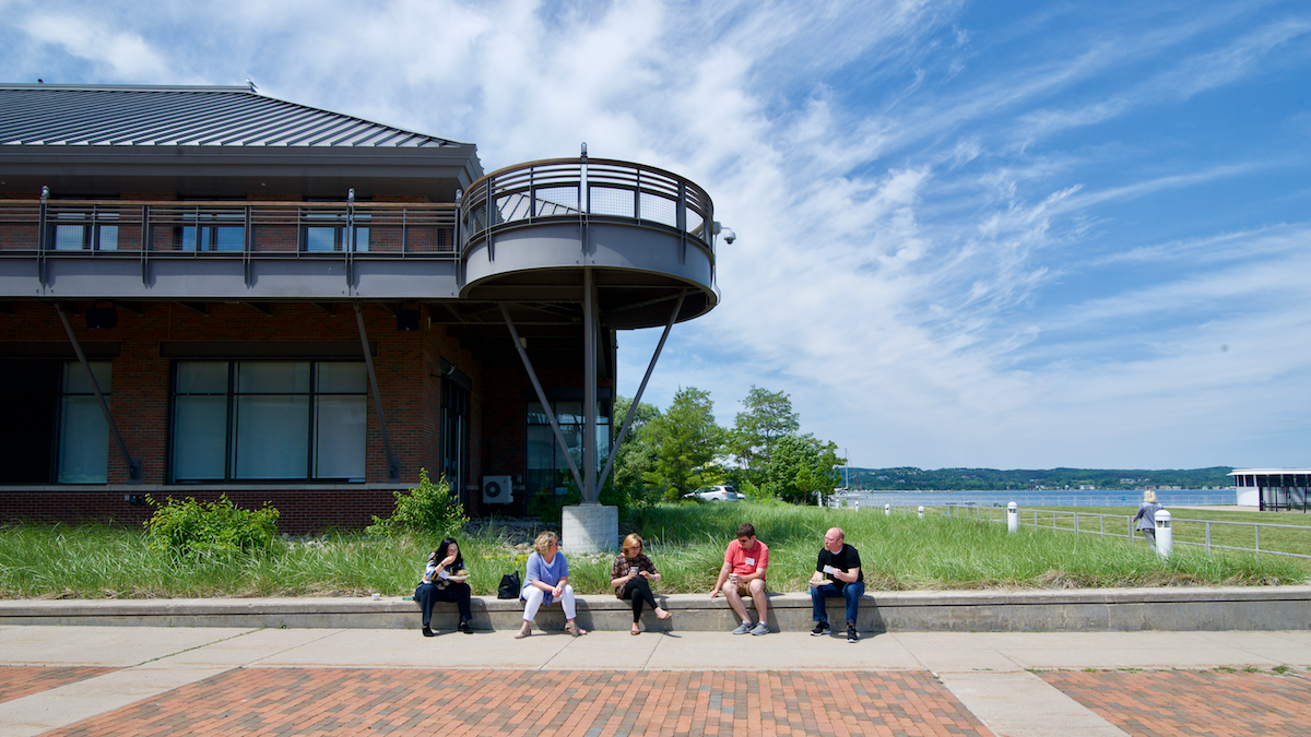 5 participants sitting outside the lodge with the lake in the background