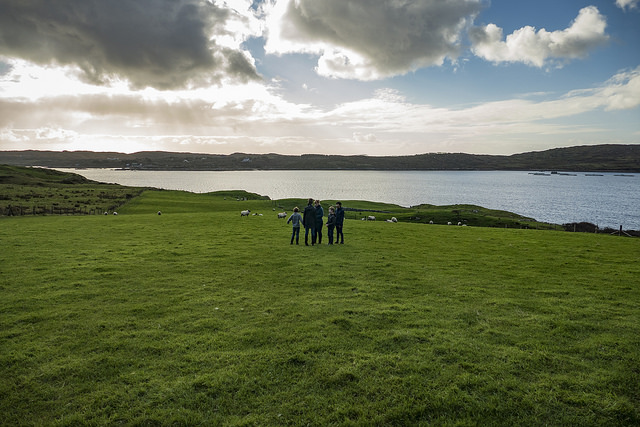 [Photo of a small group of people silhouetted against a wide emerald-green shore]