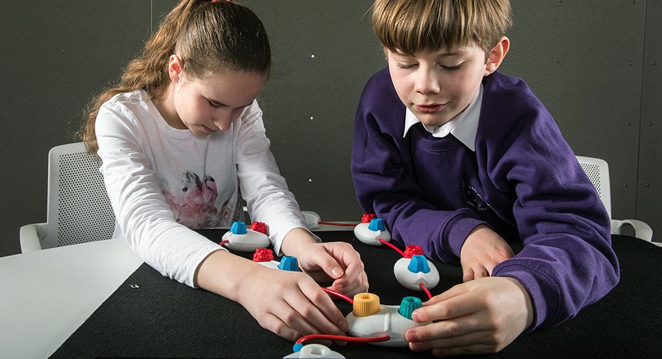 Dos niños interactúan con el lenguaje de programación táctil