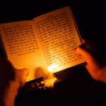 Hands holding open Hebrew book with lit candle