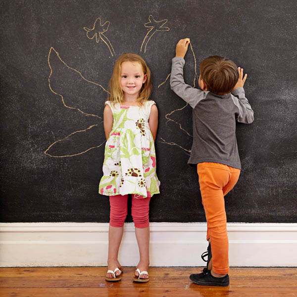 A mischievous little boy draws butterfly wings on the wall behind his happy little sister.