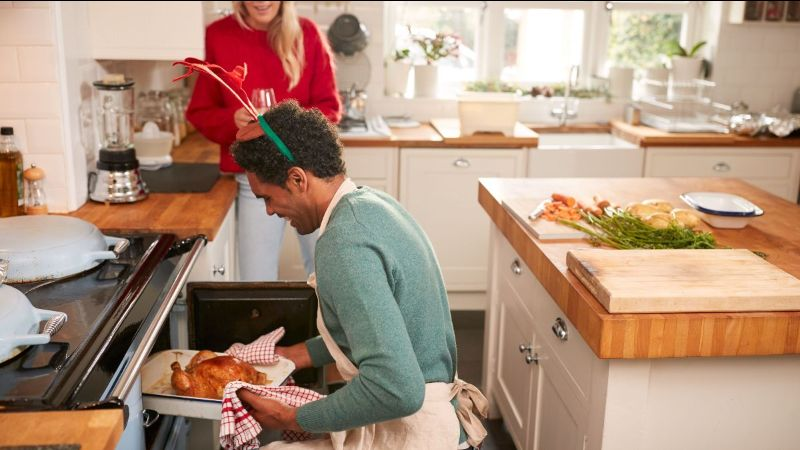 Man taking turkey out of oven on Christmas