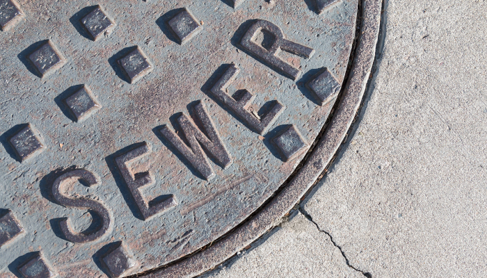 """manhole with the word """"sewer"""" engraved"""