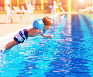 A small boy jumps into a clear, blue pool on a hot summer day.