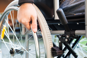 Close-up photo of a wheelchair user with his hand on the wheel