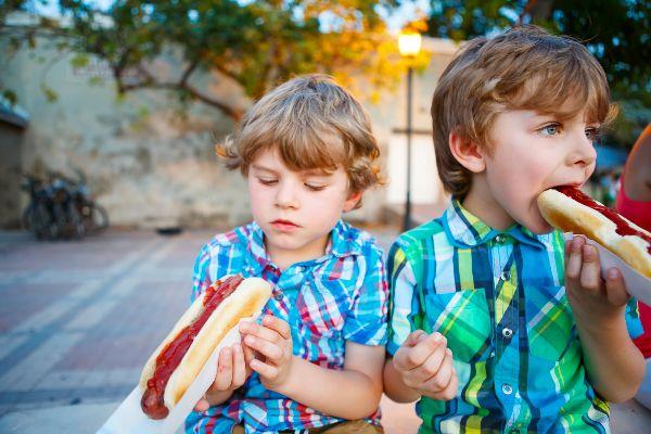 A couple of kids enjoying hotdogs in the parking lot