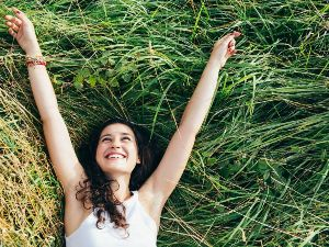 A happy young woman celebrates her scholarship in a field of long grass.