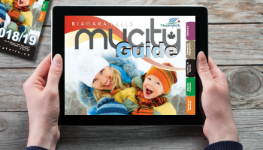 A woman holds a tablet displaying the MyCity Guide e-edition
