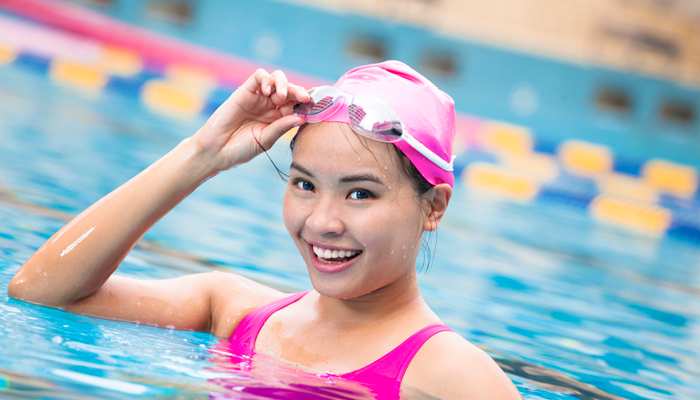 A happy young girl in a swim cap lifts her goggles and smiles from her lane in the pool.