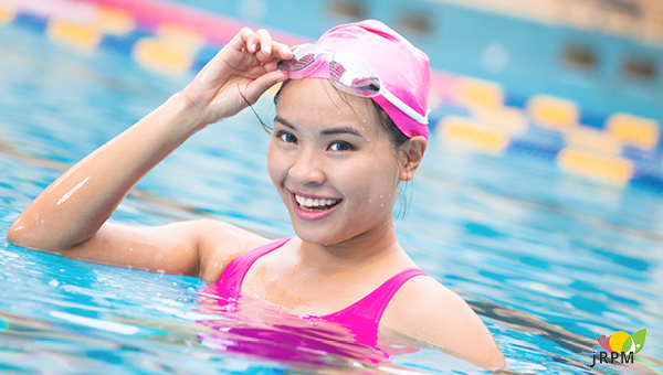 girl smiling in a pool lifting her goggles