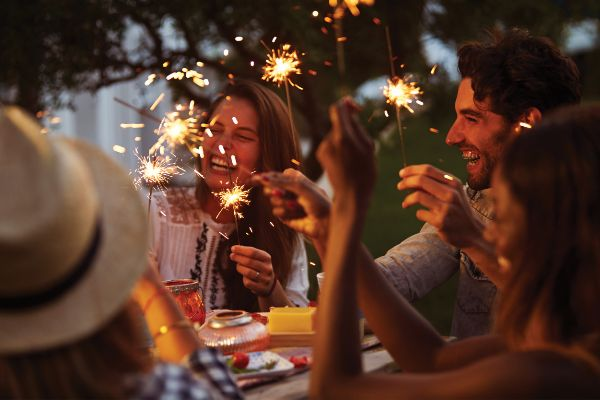 A group of friends gathered round a picnic table celebrate with sparklers at dusk.