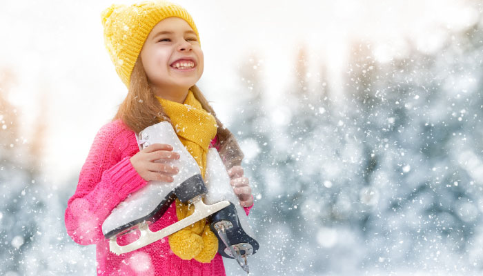 Girl smiling in the snow, holding a pair of skates
