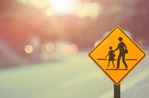 A school crossing sign at sunrise