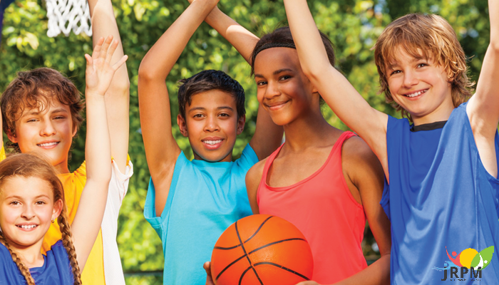 A group of happy kids on the basketball court in summertime.