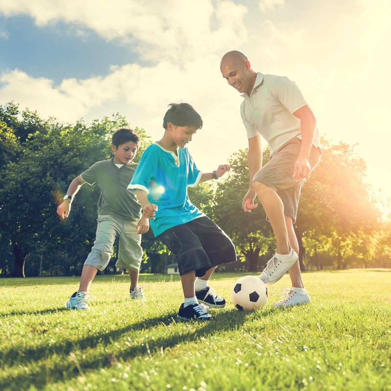A father plays soccer in the park with his two sons.