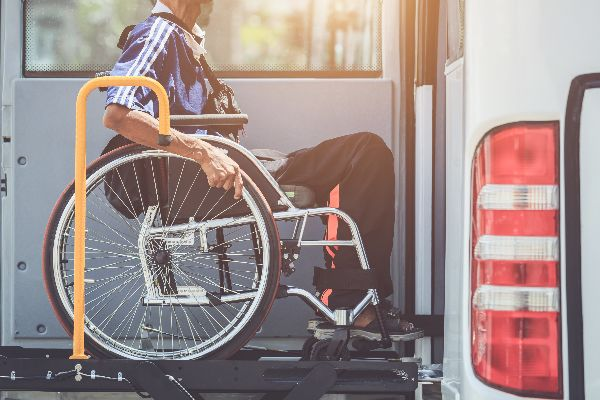 A man in a wheelchair boards a specialized transit van on a sunny day