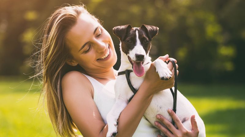 woman holding a small dog in her arms, smiling