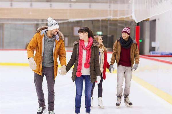 Two couples skating at an arena.