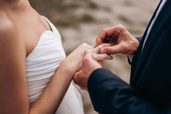 groom wears a wedding ring on the bride's finger during the wedding ceremony