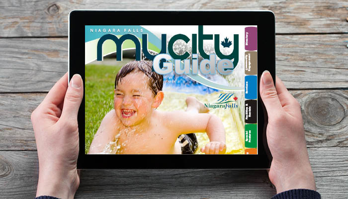 A women holds a tablet displaying the online edition of the Spring Summer 2019 MyCity Guide