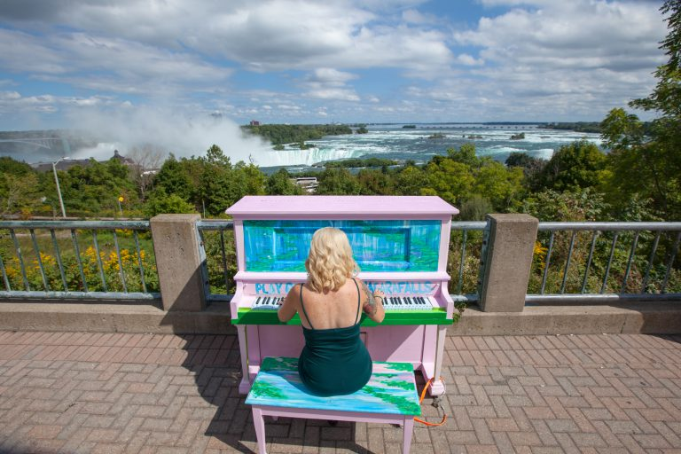 example of public art in the city - woman playing a painted piano in front of the falls