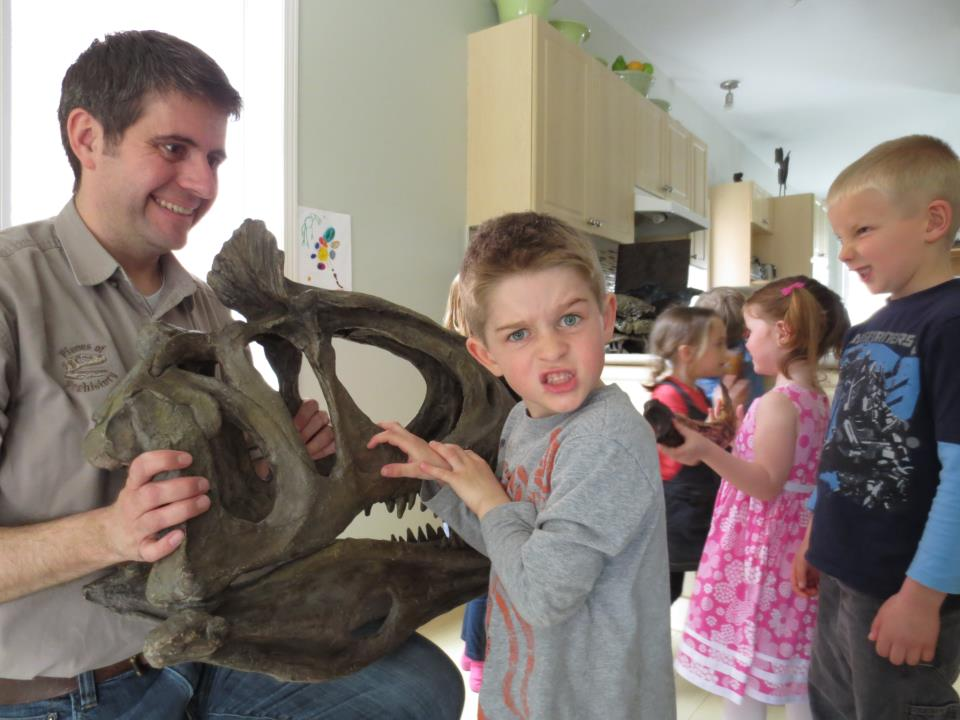 A man and some children playing with an animal skull.