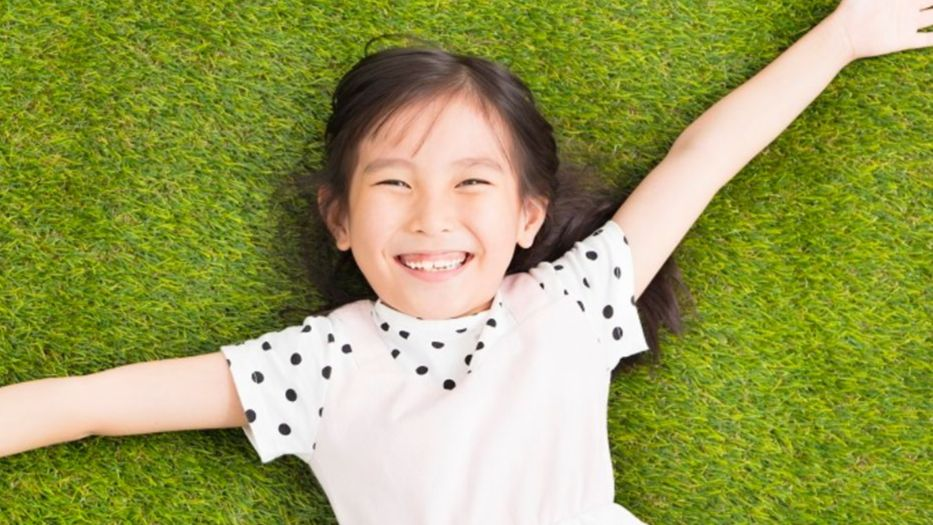 Girl laying on the grass at a park, smiling
