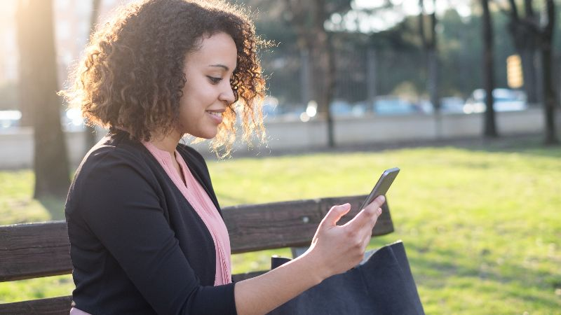 woman sitting on a bench using a smart phone