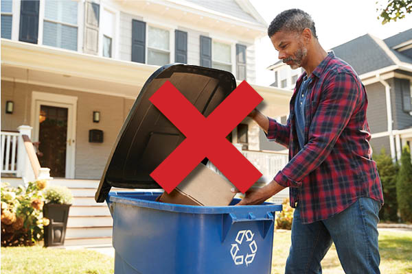 A man places a sealed box inside his blue bin. There better not be any batteries in there.
