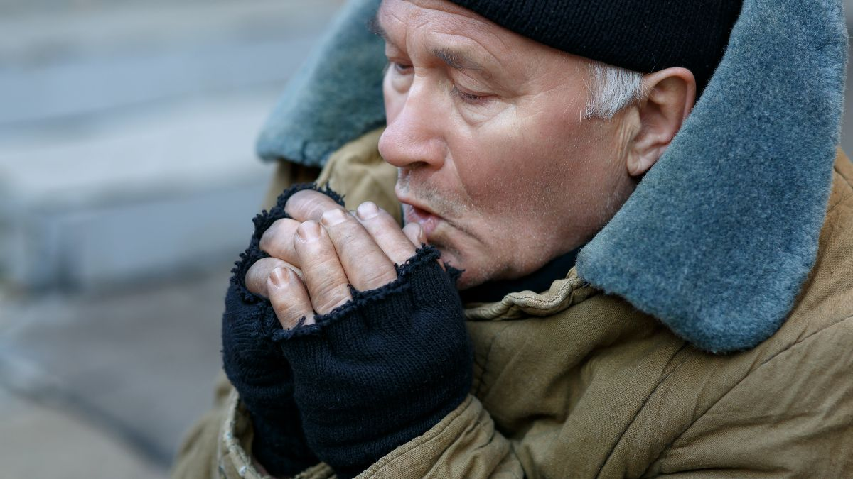 A cold, homeless, elderly man blows into his hands to warm up.