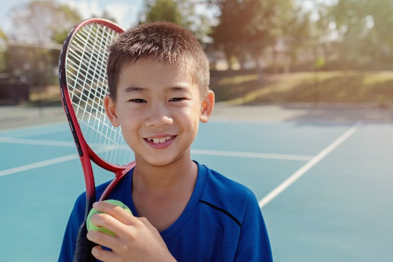 young boy tennis player on outdoor blue court