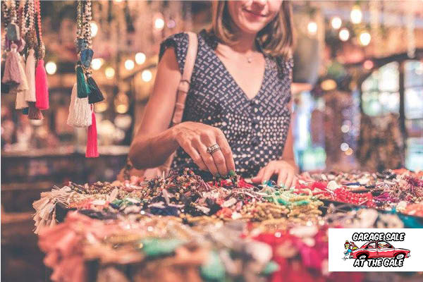 A woman browses a large jewellery collection at an outdoor market.