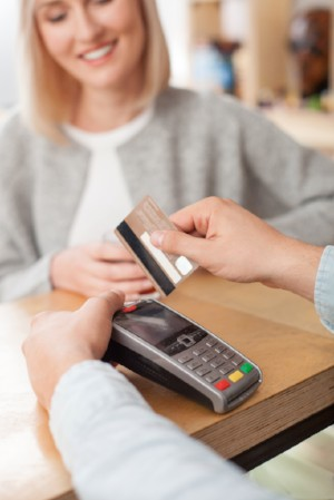 A woman makes a payment with her debit card