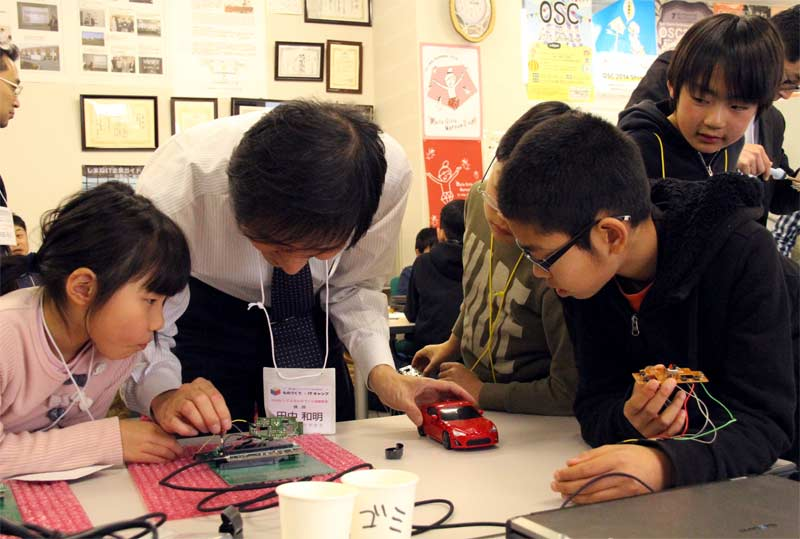 Mr. Kazuaki Tanaka and with a circuit board and students