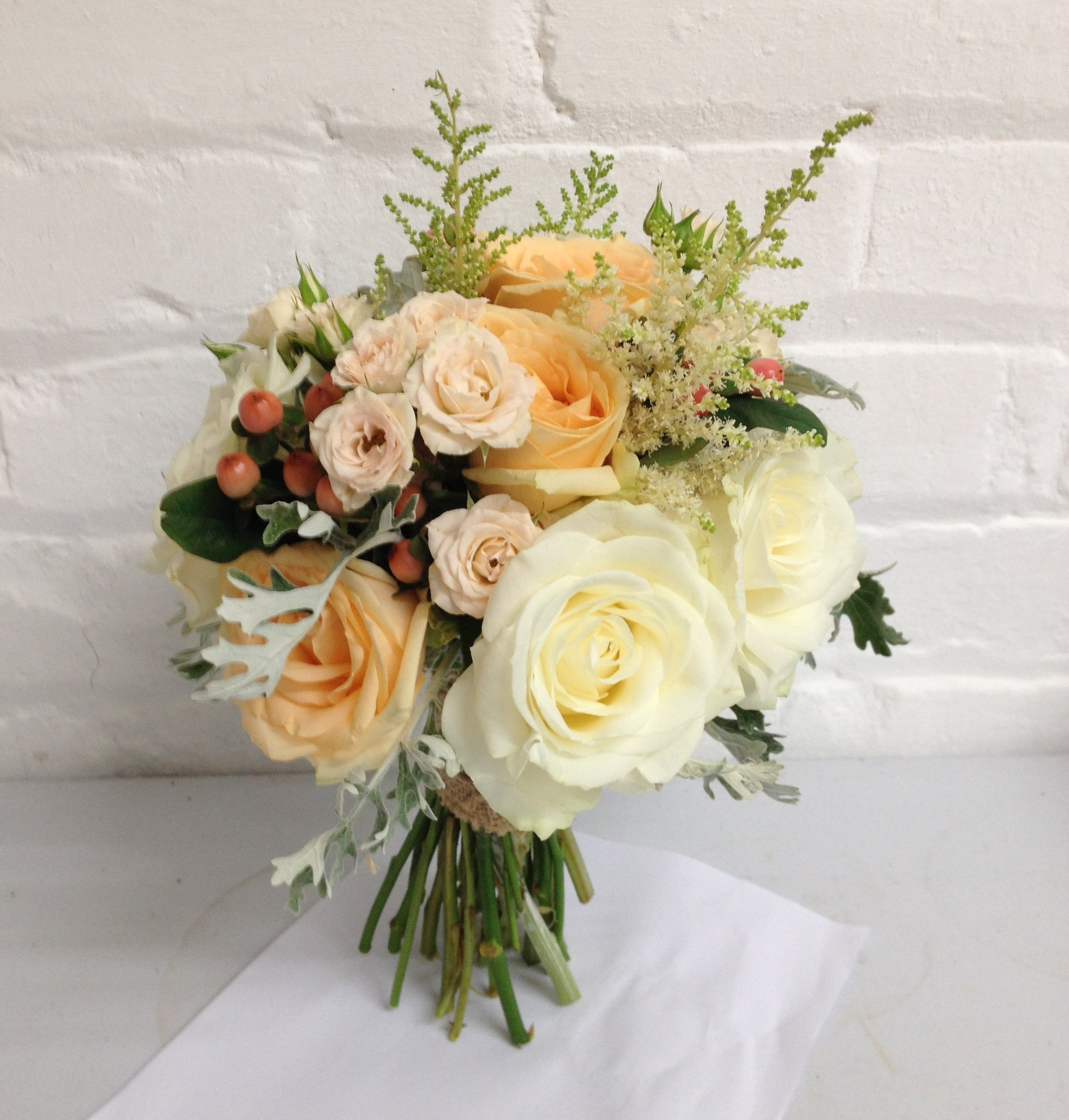 Peaches & Cream Wild Country Garden Bridal Bouquet with roses, spray roses, astilbe, hypernicum berries & grey senicio leaves Side View