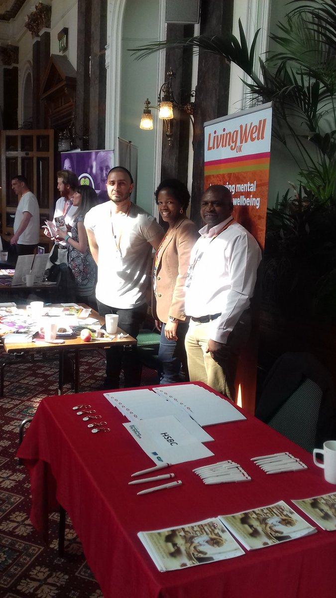 Living Well staff at promotional event with Living Well banner and publicity